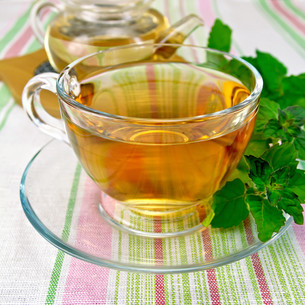 Tea with mint in cup and teapot on tableclothの写真素材 [FYI00645494]