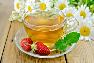Tea with strawberries and daisies on boardの写真素材 [FYI00645512]