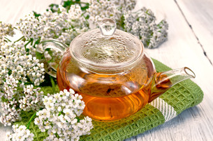 Tea with yarrow in glass teapot on napkinの写真素材 [FYI00645523]