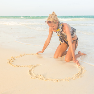 Woman drawing heart on the sand.の写真素材 [FYI00645528]