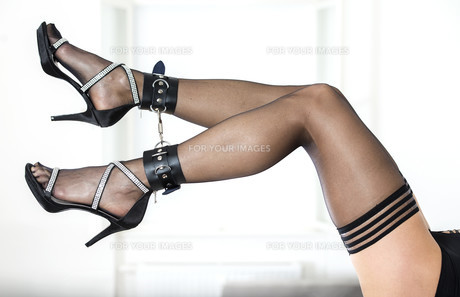 Cuffed legs of a woman wearing stockings and elegant high heelsの写真素材 [FYI00645706]
