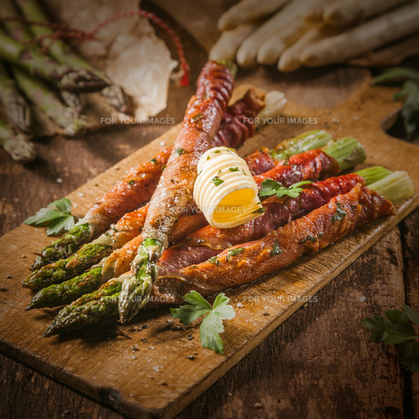 Asparagus Wrapped in Bacon with Curl of Butterの写真素材 [FYI00645902]