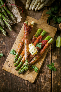 Asparagus Wrapped in Bacon with Curl of Butterの写真素材 [FYI00645903]