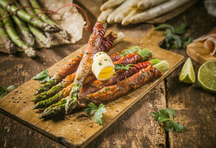 Asparagus Wrapped in Bacon with Curl of Butterの写真素材 [FYI00645904]