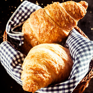 Tasty Croissant Bread on Basket with Clothの写真素材 [FYI00645934]