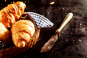 Freshly Baked Croissant and Cutting Knife on Tableの写真素材 [FYI00645940]