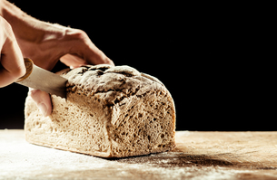 Man cutting a homemade loaf of wholegrain breadの写真素材 [FYI00645943]