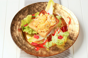 Toast and scrambled eggs on nest of fresh saladの写真素材 [FYI00646181]