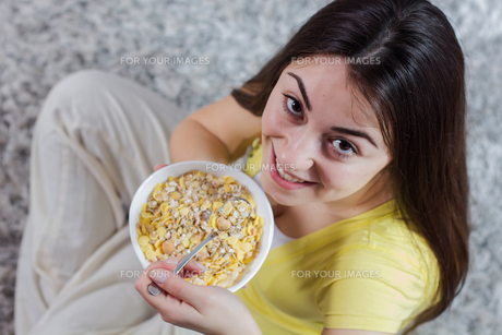 Happy Young Woman Eating Cereal Breakfastの写真素材 [FYI00646276]