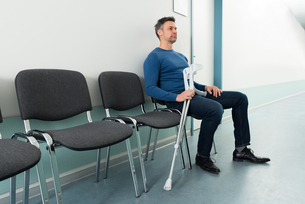 Man Sitting On Chair With Crutchesの写真素材 [FYI00646446]