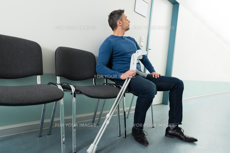 Man With Crutches Sitting On Chairの写真素材 [FYI00646448]