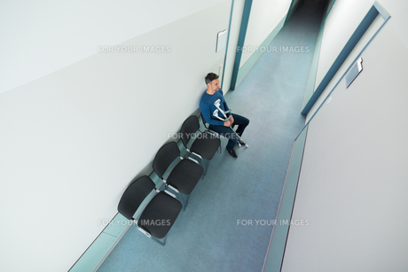 Man Sitting On Chair With Crutchesの写真素材 [FYI00646449]