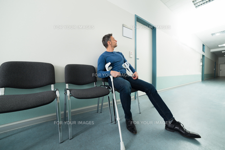 Man With Crutches Sitting On Chairの写真素材 [FYI00646450]
