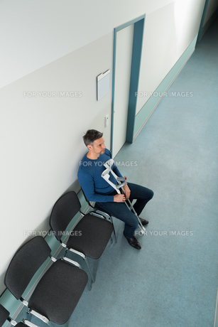 Man Sitting On Chair With Crutchesの写真素材 [FYI00646451]