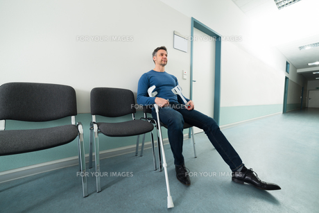 Man With Crutches Sitting On Chairの写真素材 [FYI00646453]