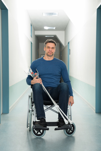 Man Sitting On Wheelchair With Crutchesの写真素材 [FYI00646454]