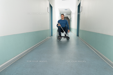 Man Sitting On Wheelchair With Crutchesの写真素材 [FYI00646457]