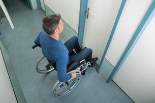 Man Sitting On Wheelchair Opening Doorの写真素材 [FYI00646463]