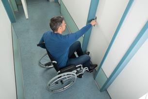 Man Sitting On Wheelchair Opening Doorの写真素材 [FYI00646464]