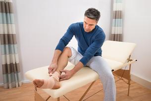 Man Tying Bandage To His Footの写真素材 [FYI00646489]