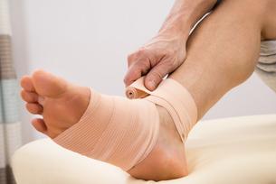 Man Putting Elastic Bandage On Footの写真素材 [FYI00646491]