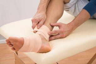 Man Putting Elastic Bandage On Footの写真素材 [FYI00646493]