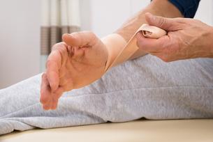Man Tying Bandage To His Wristの写真素材 [FYI00646496]