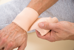 Man Tying Bandage To His Wristの写真素材 [FYI00646498]
