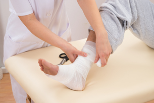 Woman Tying Bandage On Patient's Footの写真素材 [FYI00646502]