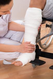 Female Doctor Holding Patient's Legの写真素材 [FYI00646504]