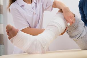 Doctor Bandaging Patient's Legの写真素材 [FYI00646506]