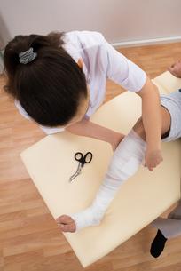 Female Doctor Bandaging Patient's Legの写真素材 [FYI00646507]