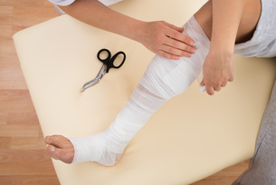 Woman Tying Bandage On Patient's Legの写真素材 [FYI00646508]