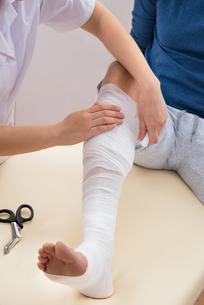 Female Doctor Bandaging Patient's Legの写真素材 [FYI00646509]