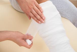 Doctor Bandaging Patient's Legの写真素材 [FYI00646516]