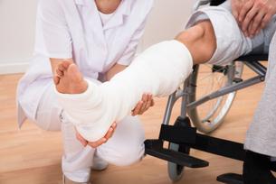 Female Doctor Holding Patient's Legの写真素材 [FYI00646520]