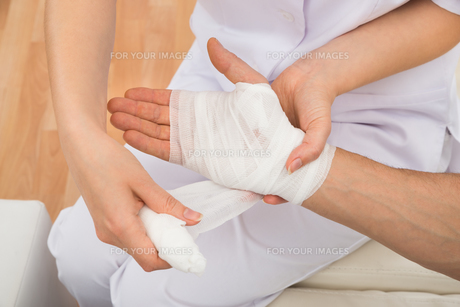 Female Doctor Bandaging Patient's Handの写真素材 [FYI00646535]
