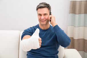 Man With Fractured Hand Showing Thumb-upの写真素材 [FYI00646544]