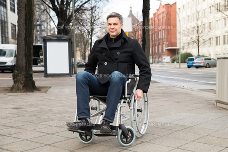 Disabled Man On Wheelchair In Cityの写真素材 [FYI00646557]
