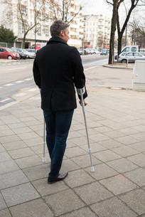 Man Walking On Street Using Crutchesの写真素材 [FYI00646578]