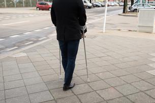 Man Walking On Street Using Crutchesの写真素材 [FYI00646579]