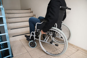 Man On Wheelchair In Front Of Staircaseの写真素材 [FYI00646580]