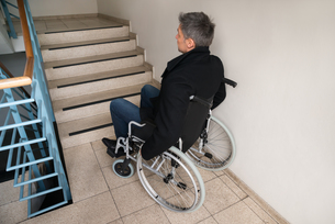 Disabled Man On Wheelchair In Front Of Staircaseの写真素材 [FYI00646586]