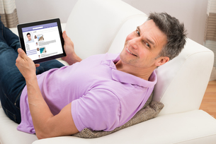Man Chatting On Social Networking Website On Couchの写真素材 [FYI00646601]