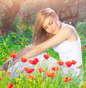 Beautiful woman on poppy flower fieldの写真素材 [FYI00646638]