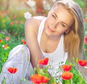 Beautiful girl on poppy flower fieldの写真素材 [FYI00646639]