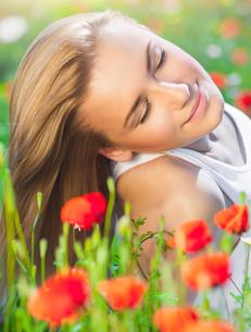Beautiful woman on poppy flower fieldの写真素材 [FYI00646641]