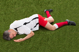 Soccer Player Lying On Grassの写真素材 [FYI00646680]