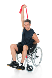 Disabled Man On Wheelchair Stretching With Resistance Bandの写真素材 [FYI00646710]