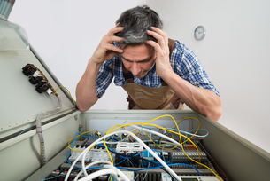 Confused Electrician Looking At Fuse Boxの写真素材 [FYI00646721]